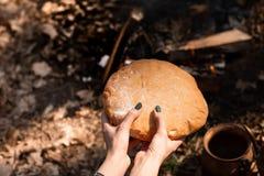 Closeup av nytt rustsic bröd i en kvinnas hand Bakgrunden av skogen royaltyfri foto
