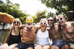 Closeup av olika höga vuxna människor som sitter av pölen som tycker om su royaltyfria foton