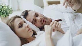 Closeup av par med förhållandeproblem som har emotionell konversation, medan ligga i säng hemma lager videofilmer