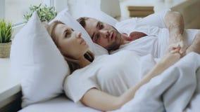 Closeup av par med förhållandeproblem som har emotionell konversation, medan ligga i säng hemma Vänd för ung kvinna stock video