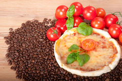Closeup av pizza med kaffebönor, tomater, ost och basilika på träbakgrund Royaltyfri Fotografi