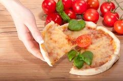 Closeup av pizza med tomat-, ost-, basi- och kvinna handsl på träbakgrund Royaltyfri Fotografi
