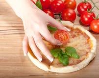 Closeup av pizza med tomat-, ost-, basi- och kvinna handsl på träbakgrund Arkivfoto