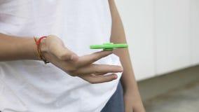 Closeup av pojken som spelar med den gröna rastlös människaspinnaren - stock video