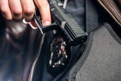 Closeup av polisen som ut tar handeldvapnet från pistolhölster på nig royaltyfria bilder