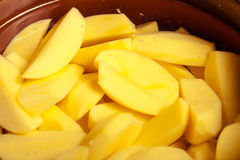 Closeup av rå skalade potatisar i kruka eller panna. Sund mat. Arkivfoto