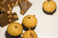 Closeup av sötsaker, choklad med muttrar och muffin på en vit bakgrund arkivbild