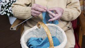 Closeup av sammanträde och handarbete för äldre kvinna royaltyfri foto