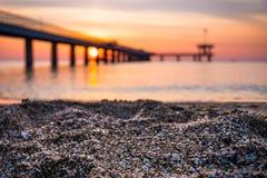 Closeup av sand på stranden Suddig soluppgång över en havsbro i bakgrunden Royaltyfri Bild