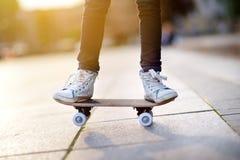 Closeup av skateboarderben Utomhus- ungeridningskateboard royaltyfri foto