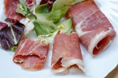closeup av skivor av rullande kurerad grisköttskinkajamon med grönsallat Royaltyfri Foto