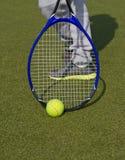 Closeup av skor med den tennisracket och bollen utomhus Royaltyfria Foton
