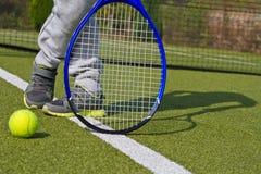 Closeup av skor med den tennisracket och bollen utomhus Royaltyfri Foto