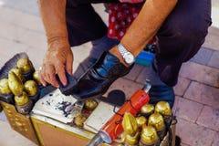 Closeup av skosken i gatan på svarta läderskor arkivfoto