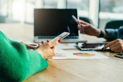 Closeup av smartphonen i händer för kvinna` s Ungt affärskvinnasammanträde på tabellen och brukssmartphonen arkivfoto