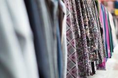 Closeup av sortimentet av varma tillfälliga kläder som hänger på hängare arkivbild