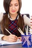 Closeup av studentsammanträde på hennes skrivbord som koncentreras och göras H arkivfoto