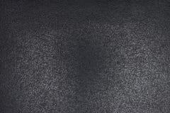 Closeup av svart grov bakgrund som tänds med dunkelt ljus arkivbild