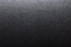 Closeup av svart grov bakgrund som tänds med dunkelt ljus arkivfoton