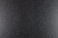 Closeup av svart grov bakgrund som tänds med dunkelt ljus royaltyfria bilder