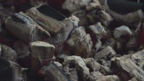 Closeup av tända stycken av kol som täckas av grå aska i stor svart fyrpanna stock video