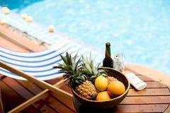 Closeup av tropiska frukter i träkorg vid poolsiden Royaltyfri Bild