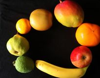 Closeup av tropiska frukter mot svart bakgrund royaltyfri fotografi