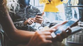 Closeup av unga coworkers som använder elektroniska grejer i soligt kontor Man att rymma en smartphone hans händer och kvinna Arkivfoton