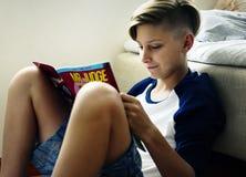 Closeup av ungt caucasian mansammanträde på den läs- vagnen för golv royaltyfria bilder