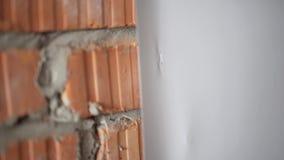 Closeup av väggen för röd tegelsten med gråa konkreta och vita tapeter med häftklamrar stock video