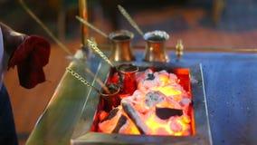 Closeup av varmt kaffe som är förberedd i turk på öppen brand arkivfilmer