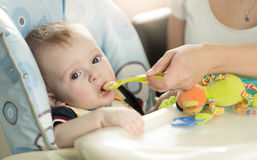 Closeup of baby boy eating puree from spoon Stock Photo