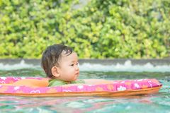 Closeup a baby boy sit in a boat for children in the swimming pool background. Closeup baby boy sit in a boat for children in the swimming pool background royalty free stock photography