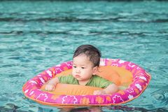 Closeup a baby boy sit in a boat for children in the swimming pool background. Closeup baby boy sit in a boat for children in the swimming pool background stock image