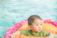 Closeup a baby boy sit in a boat for children in the swimming pool background. Closeup a baby boy sit in boat for children in the swimming pool background stock photos