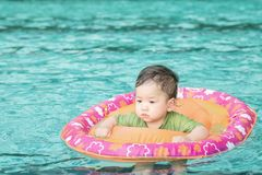 Closeup a baby boy sit in a boat for children in the swimming pool background Royalty Free Stock Image