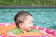 Closeup a baby boy sit in a boat for children in the swimming pool background. Closeup a baby boy sit in boat for children in the swimming pool background royalty free stock photo