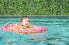 Closeup asian baby boy sit in a boat for children in the swimming pool background with smile face in happy emotion Stock Photo