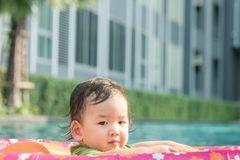 Closeup a baby boy sit in a boat for children in the swimming pool and building view background. Closeup baby boy sit in a boat for children in the swimming pool royalty free stock photo