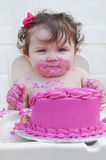 Closeup of a baby girl eating her 1st birthday c. Baby girl eating first birthday cake with pink frosting and bow in her hair stock images