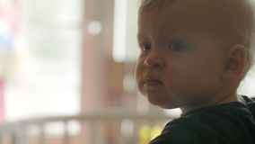 A closeup of a baby girls face who is thoughtfully looking into the distance stock video