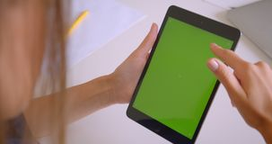 Closeup back portrait of young attractive caucasian woman using tablet with green chroma screen in office indoors.  stock footage