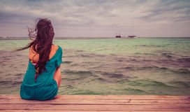 Closeup back view of long hair woman. Sitting in blue beach dress looking out towards blue ocean and sky. Retro style color tones Stock Photo