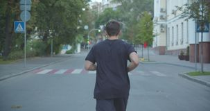 Closeup back view portrait of adult caucasian sporty male jogger walking down the street in the urban city outdoors stock video footage