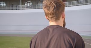 Closeup back view portrait of adult caucasian sporty male jogger walking on the stadium in the urban city outdoors stock video