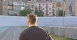 Closeup back view portrait of adult caucasian sporty male runner jogging on the stadium in the urban city outdoors stock footage