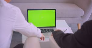 Closeup back view portrait of two businessmen using laptop with green chroma screen and celebrating success in the. Office indoors stock video footage