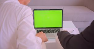 Closeup back view portrait of two businessmen using laptop with green screen having discussion in the office indoors.  stock video footage