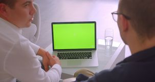 Closeup back view portrait of two businessmen using laptop with green screen having a meeting sitting in armchairs in. Office indoors stock video footage