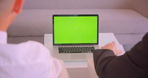 Closeup back view portrait of two businessmen using laptop with green screen in the office indoors.  stock footage